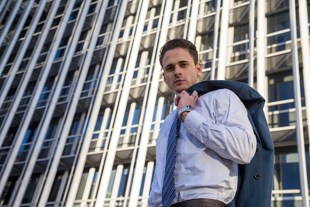 Zakenman die in elegant kostuum zijn jasje op achtergrond van moderne bureauwolkenkrabber houdt.