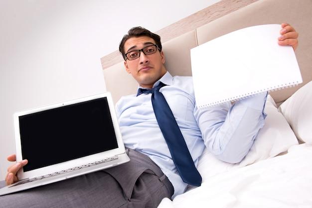 Zakenman die in het bed thuis werkt