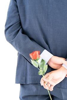 Zakenman die in kostuum rode rozen achter zijn rug houdt Premium Foto