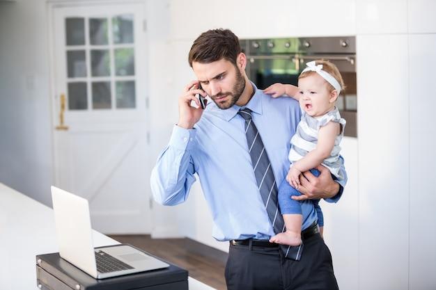 Zakenman die in laptop kijkt terwijl het dragen van dochter