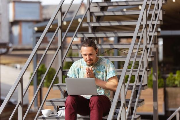 Zakenman die in openlucht met laptop werkt, die aan het computerscherm kijkt