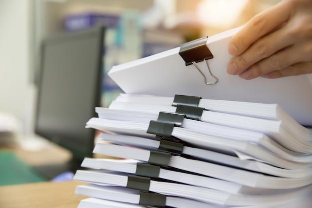 Zakenman die in stapeldocument werken voor het zoeken van informatie over bureaubureau.