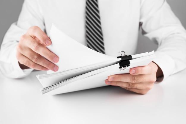 Zakenman die in stapels papieren dossiers werkt die naar informatie zoeken