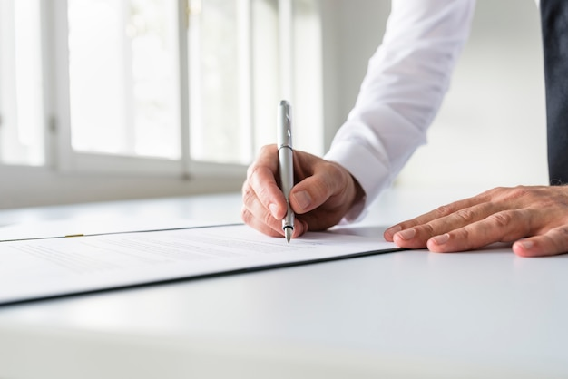 Zakenman die in wit overhemd contract ondertekenen