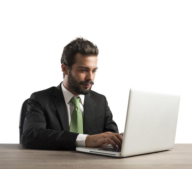 Zakenman die in zijn bureau met laptop werkt
