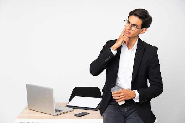 Zakenman die in zijn bureau over geïsoleerde witte muur een idee denkt