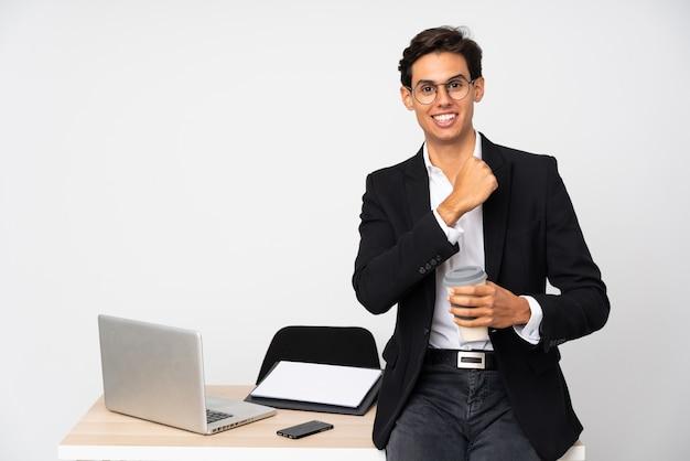 Zakenman die in zijn bureau over geïsoleerde witte muur een overwinning viert