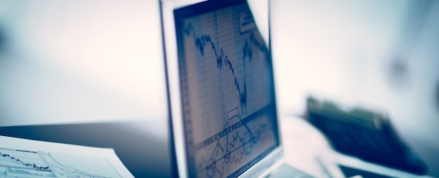 Zakenman die investeringsgrafieken met laptop analyseert. boekhouding