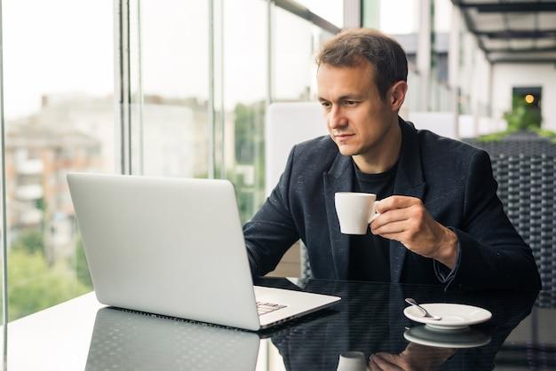 Zakenman die koffie drinkt en zijn werk doet op laptop in café