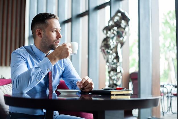 Zakenman die koffie drinkt terwijl hij aan nieuw project denkt.