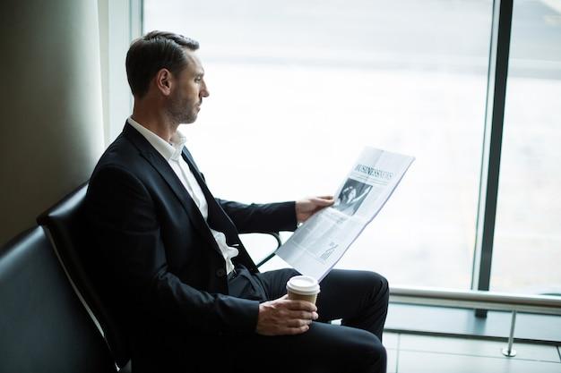 Zakenman die koffie heeft tijdens het lezen van krant in wachtruimte