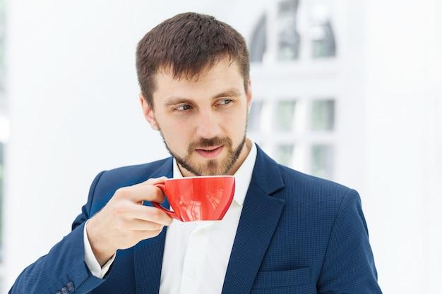 Zakenman die koffiepauze heeft, houdt hij een kop