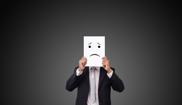 Zakenman die kostuum met de emotiegevoelens van tekeningsexpressies op witboek dragen