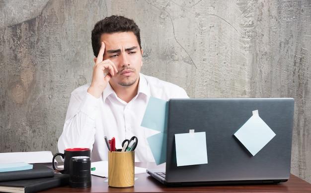Zakenman die laptop bekijkt bij het bureau.