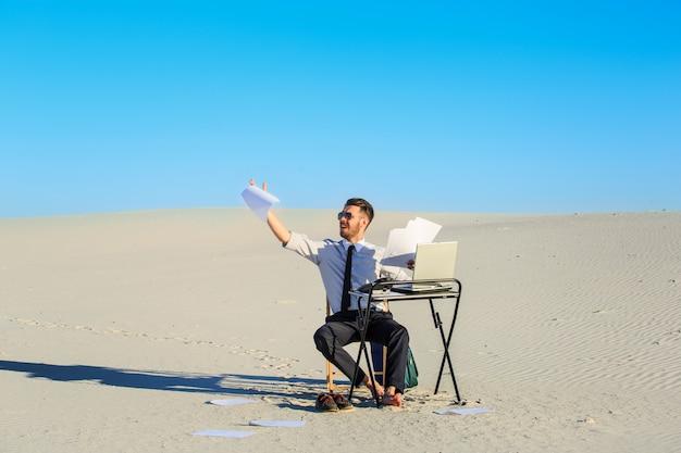 Zakenman die laptop in een woestijn met behulp van