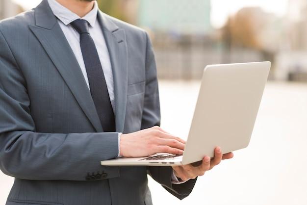Zakenman die laptop in openlucht met behulp van