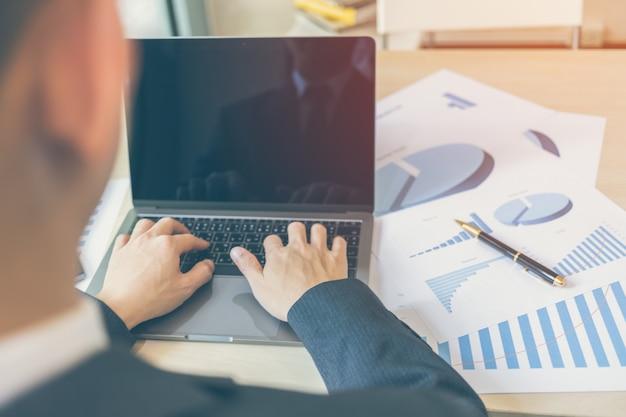 Zakenman die laptop of notitieboekje met grafiekdocument bedrijfsdocumenten typt