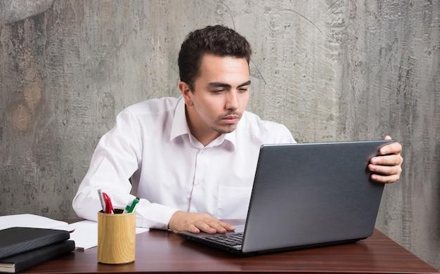 Zakenman die laptop onderzoekt en aan de balie zit. hoge kwaliteit foto