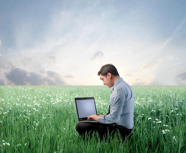 Zakenman die laptop op een weide met behulp van