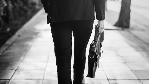 Zakenman die loopt en zijn tas vasthoudt