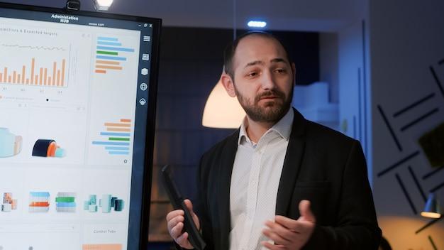 Zakenman die managementstatistieken presenteert met behulp van presentatiemonitor 's avonds laat