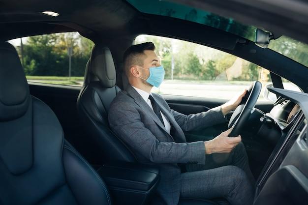 Zakenman die medisch masker draagt ter preventie van coronavirus en zijn auto naar zijn werk rijdt