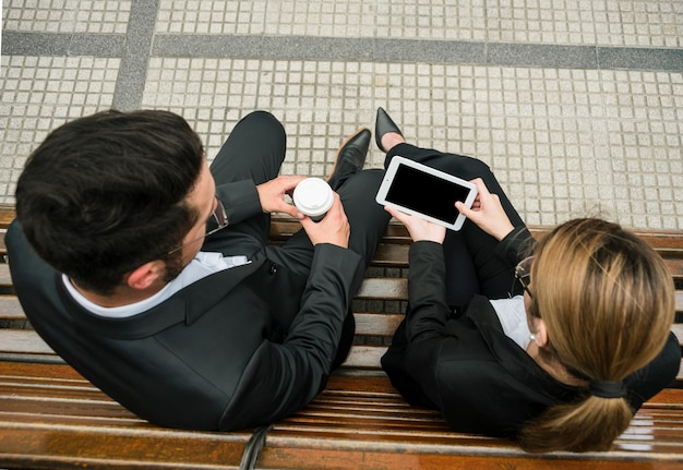 Zakenman die meeneemkoffiekop houdt die mobiele telefoongreep door onderneemster bekijkt