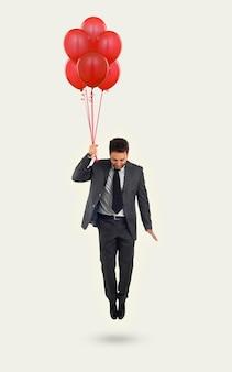 Zakenman die met ballons op wit vliegt