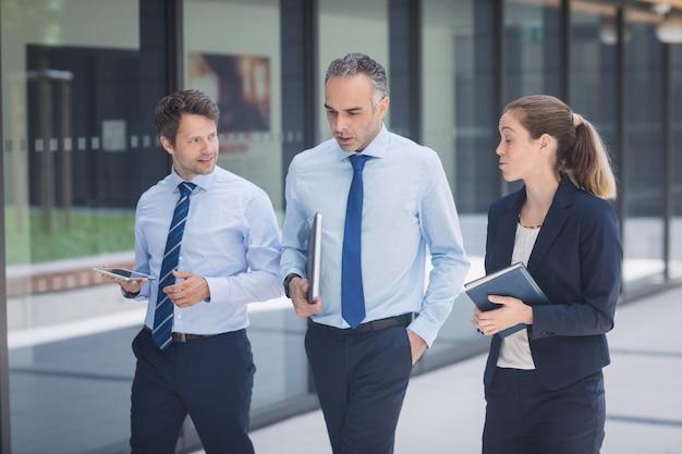 Zakenman die met collega's buiten de bureaubouw lopen