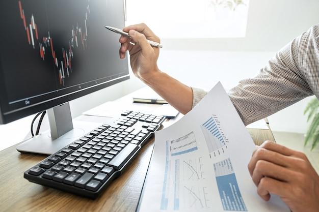 Zakenman die met computer werkt en grafiek beurs handel met de gegevens van de voorraadgrafiek analyseert