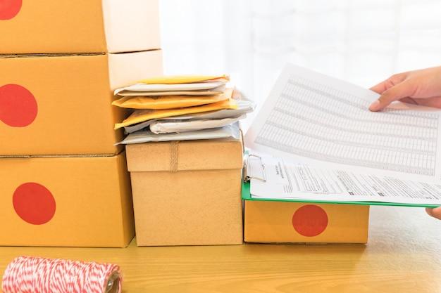 Zakenman die met document en verpakkings bruine pakjesdoos werken.