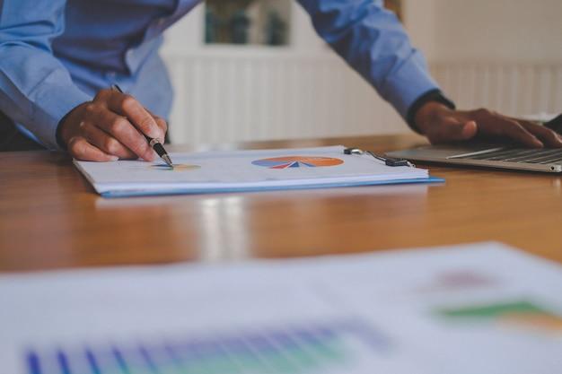 Zakenman die met document werkt, startmens analyseert financiële gegevens op werkplek,