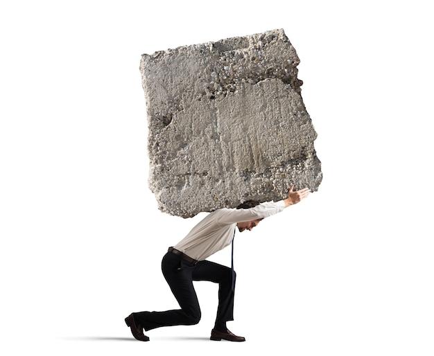 Zakenman die met een zwaar rotsblok op zijn rug loopt