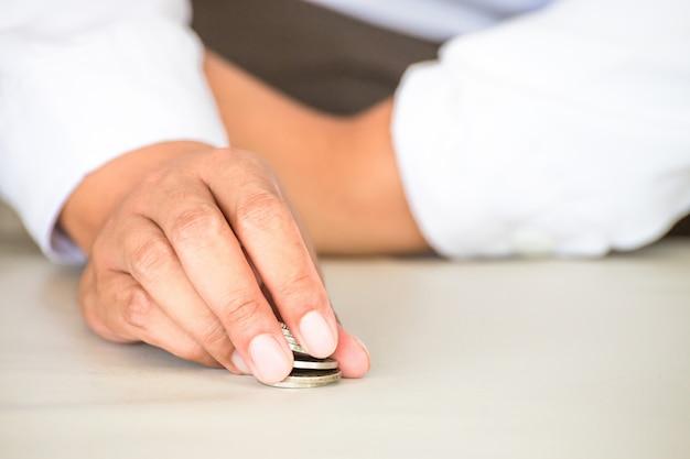Zakenman die met gouden muntstuk, tablet en mobiele telefoon op kantoor werken.