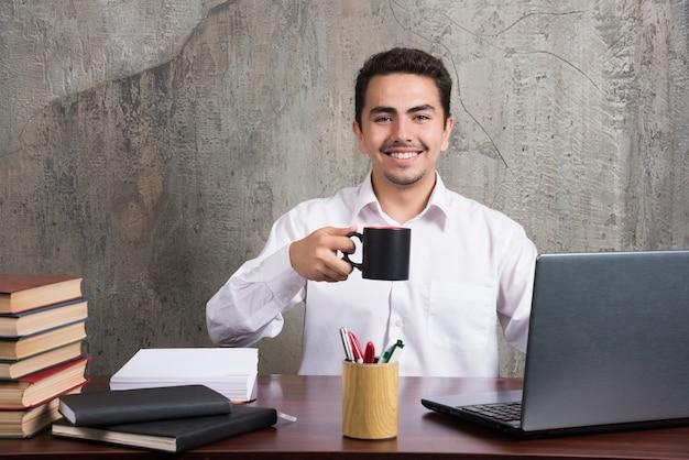 Zakenman die met kop thee bij het bureau glimlacht.