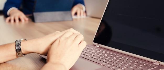 Zakenman die met laptop in seminarieruimte werkt