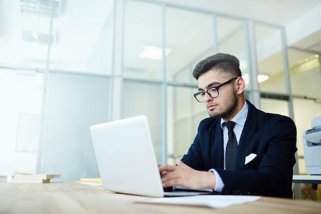 Zakenman die met laptop op kantoor werkt