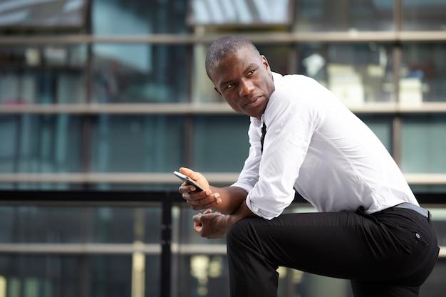 Zakenman die met mobiel en laptop in stedelijk milieu werkt