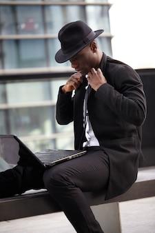 Zakenman die met mobiel en laptop werkt