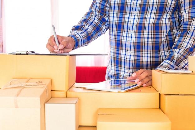 Zakenman die met mobiele telefoon werken en bruin pakjesvakje thuis kantoor inpakken. handen verkoper bereiden product klaar voor levering aan klant. online verkopen, e-commerce start verzending concept.