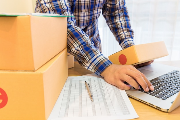Zakenman die met mobiele telefoon werken en bruin pakjesvakje thuis kantoor inpakken.