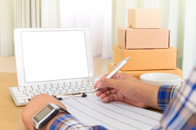 Zakenman die met mobiele telefoon werken en thuis bruine pakjesdoos inpakken. handen verkoper bereid product klaar voor levering aan klant. online verkoop, e-commerce start-up verzendconcept.