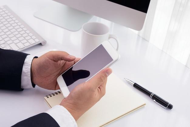 Zakenman die met moderne apparaten, computer en mobiele telefoon werkt