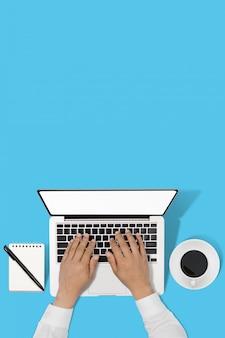 Zakenman die met moderne werkplaats met laptop aan blauwe lijst werkt,