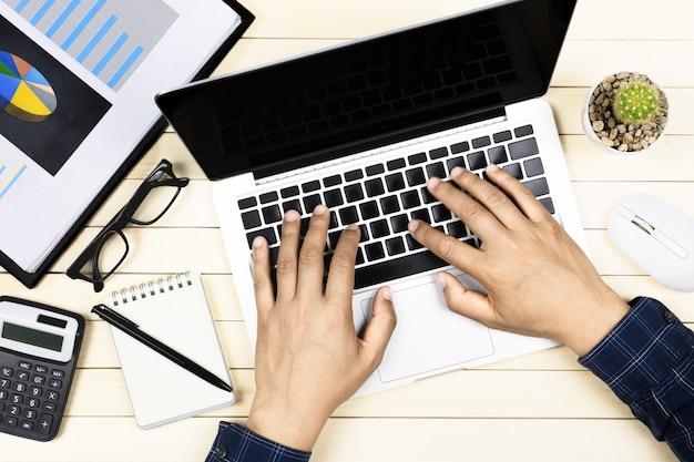 Zakenman die met moderne werkplaats met laptop aan houten lijst werkt