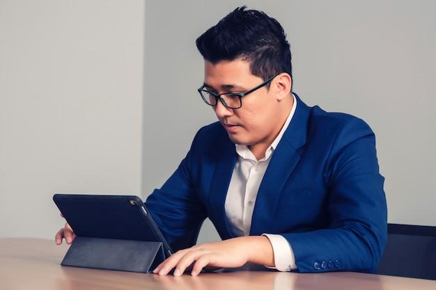 Zakenman die met tablet in seminarieruimte werkt