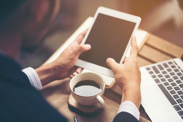 Zakenman die met tablet, online zaken werkt