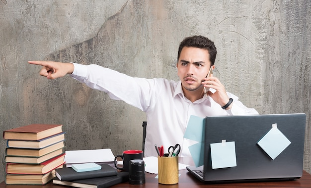 Zakenman die met telefoon spreekt en zijn kant op het bureau richt.
