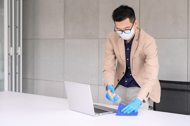 Zakenman die microfiberdoek en de spray van het alcoholdesinfecterende middel gebruiken om laptop en lijst schoon te maken