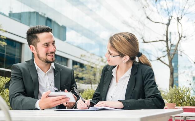 Zakenman die mobiele in hand houdt bekijkend haar collega die op het document schrijft